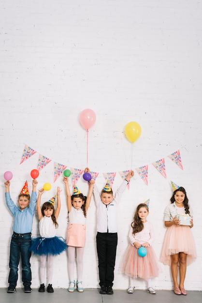 Grupo de niños de pie contra la pared disfrutando de la fiesta de cumpleaños. Foto gratis