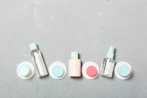 Grupo de pequeñas botellas para viajar sobre fondo gris. copyspace para tus ideas. composición plana de productos cosméticos. vista superior de envases de crema con almohadillas de algodón Foto Premium