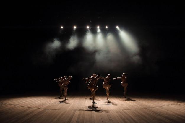Un grupo de pequeños bailarines ensaya en el escenario con luz y humo. Foto Premium