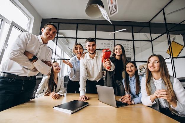 Grupo de personas arrojando dinero en una oficina Foto gratis
