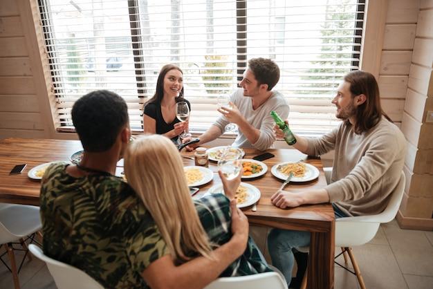 Grupo de personas cenando y hablando en la cocina Foto Premium
