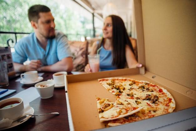 Grupo de personas comiendo pizza en café Foto gratis