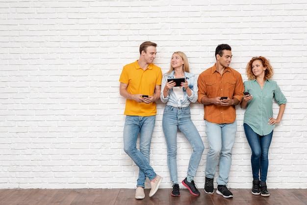 Grupo de personas con dispositivos electrónicos. Foto Premium