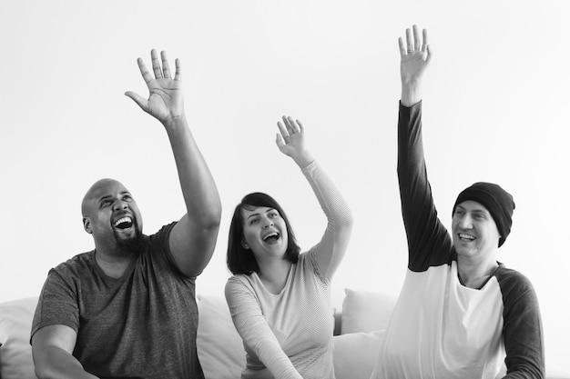 Grupo de personas diversas levantando sus manos Foto gratis