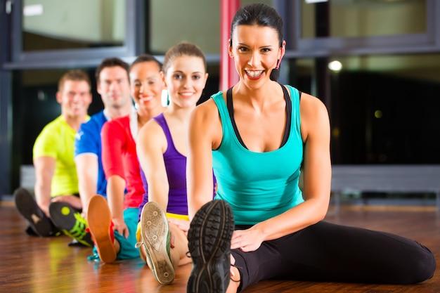 Grupo de personas e instructor en estiramientos de gimnasio Foto Premium
