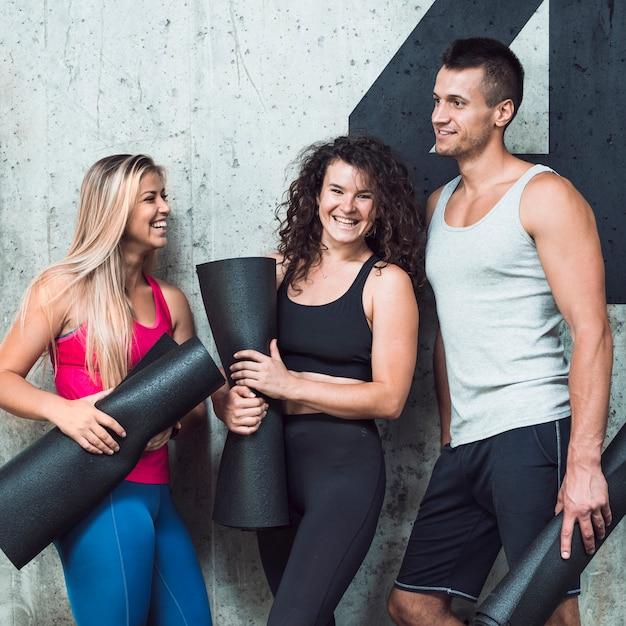 Grupo de personas felices con alfombra de fitness Foto gratis