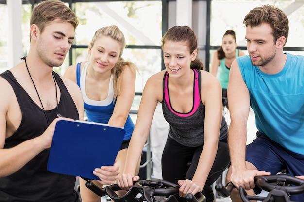 Grupo de personas en forma usando bicicleta juntos en el gimnasio Foto Premium