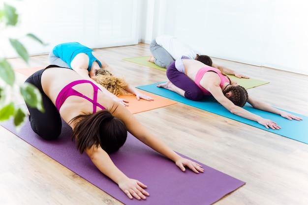 Grupo de personas practicando yoga en casa. pose de balasana.