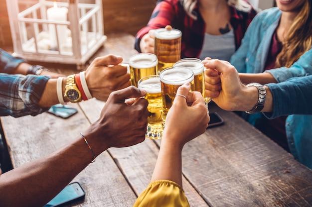 Grupo de personas que disfrutan y tuestan una cerveza en cervecería pub - concepto de amistad con jóvenes que se divierten juntos Foto Premium