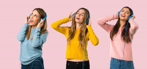 Grupo de personas con ropa colorida que escucha música con auriculares en backg colorido Foto Premium