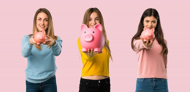 Grupo de personas con ropa colorida sosteniendo una alcancía en colores de fondo Foto Premium