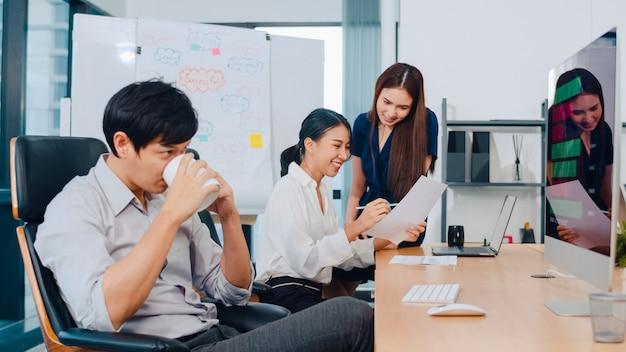 Grupo de proceso colaborativo de empresarios multiculturales en ropa casual elegante que se comunican y usan tecnología mientras trabajan juntos en una oficina creativa. el equipo asiático de jóvenes profesionales trabaja. Foto gratis