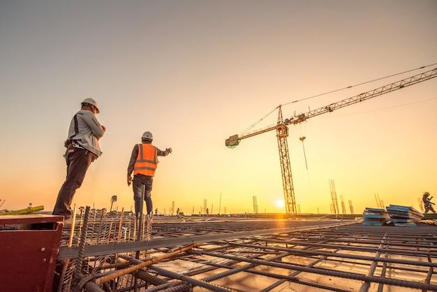 Grupo de silueta de trabajador e ingeniero civil en uniforme de seguridad instalan acero reforzado Foto Premium