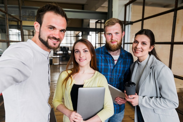 Grupo de sonrientes felices jóvenes empresarios Foto gratis