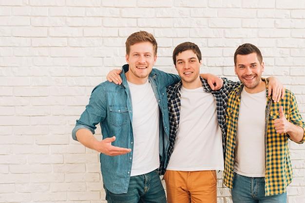 Grupo de tres amigos varones de pie juntos contra la pared blanca Foto gratis
