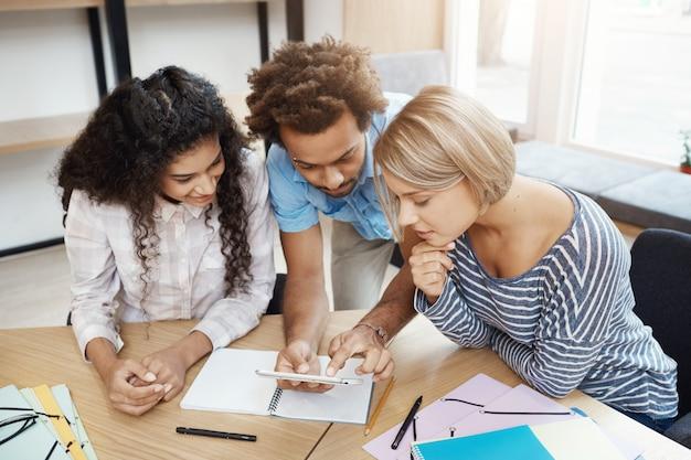Grupo de tres jóvenes emprendedores trabajando juntos en un nuevo proyecto de inicio. jóvenes sentados en la biblioteca mirando a través de información sobre el teléfono inteligente. Foto gratis