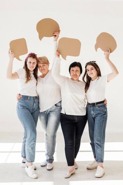 Grupo de unión de mujeres sosteniendo burbujas de chat Foto gratis