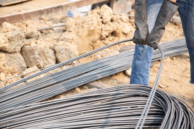 Un grupo de varillas de acero apretadas por la cadena y elevar en el sitio de construcción Foto gratis