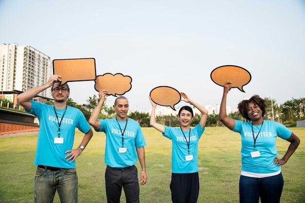 Grupo de voluntarios felices y diversos con burbujas de discurso Foto gratis