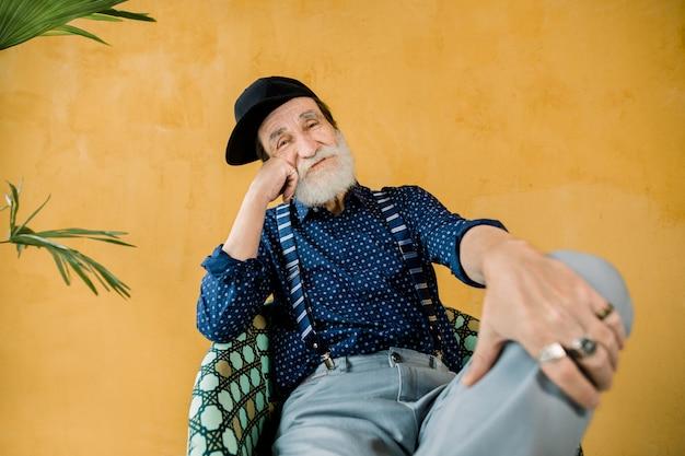Guapo, alegre, moderno, hombre mayor, con barba bien arreglada, vestido con camisa azul oscuro, tirantes, pantalones grises y gorra hipster negra, sentado en una silla en el estudio frente a la pared amarilla Foto Premium