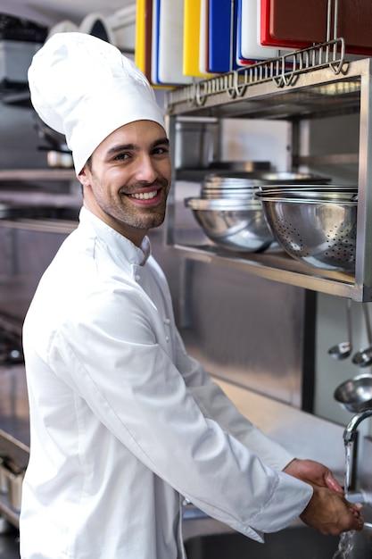 Guapo chef lavándose las manos Foto Premium