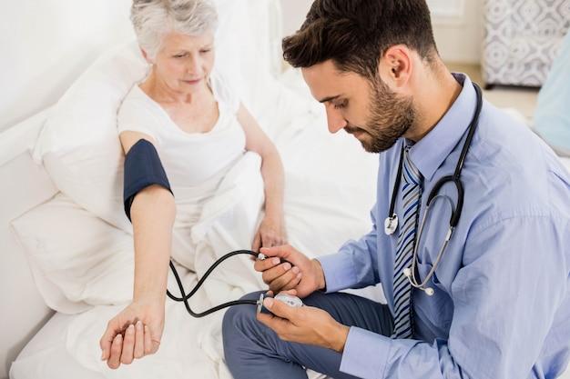 Guapo enfermera comprobando la presión arterial de una anciana en casa Foto Premium