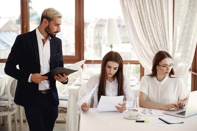Guapo inspector de restaurante con documentos y dos asistentes femeninas Foto gratis