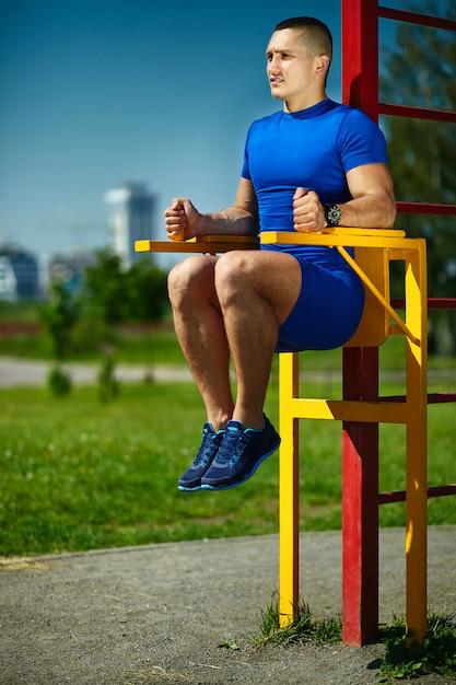 Guapo sano feliz atleta srtong hombre masculino haciendo ejercicio en el parque de la ciudad - conceptos de fitness en un hermoso día de verano en la barra horizontal Foto gratis