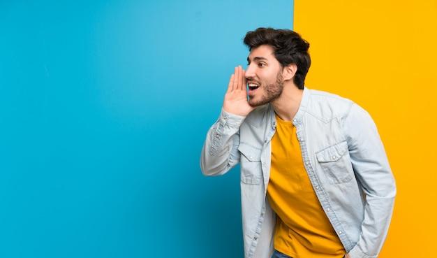 Guapo sobre aislado colorido gritando con la boca abierta al lateral Foto Premium