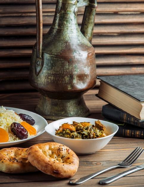 Guarnición de arroz, bollos de pan tandir y ensalada verde sobre una mesa Foto gratis