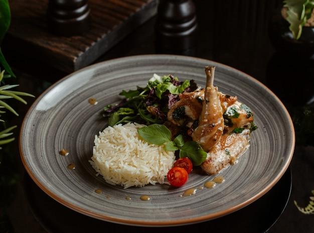 Guarnición de arroz con muslo de pollo a la parrilla picante en un plato de granito Foto gratis