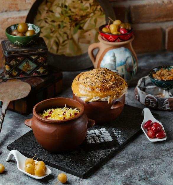 Guarnición de arroz tradicional del cáucaso con hierbas dentro de un recipiente de cerámica servido con pan Foto gratis