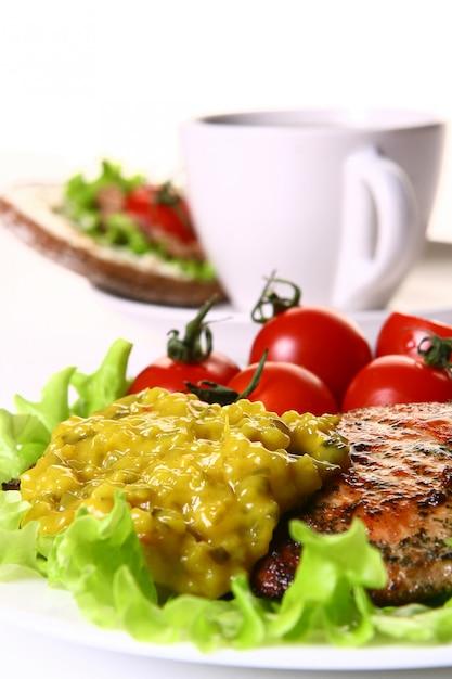 Guarnición de comida con filete y verduras y café. Foto gratis