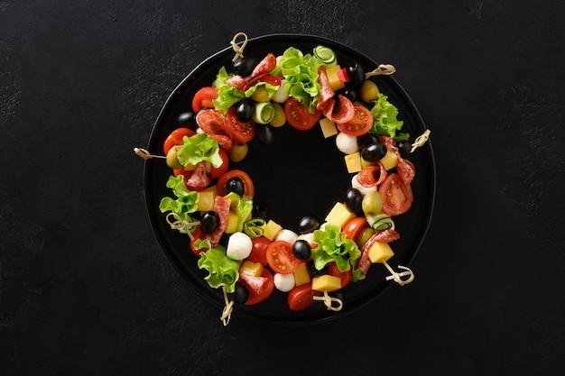 Guirnalda de comida navideña de aperitivos navideños canapés verduras queso mozzarella para la fiesta de navidad festiva Foto Premium