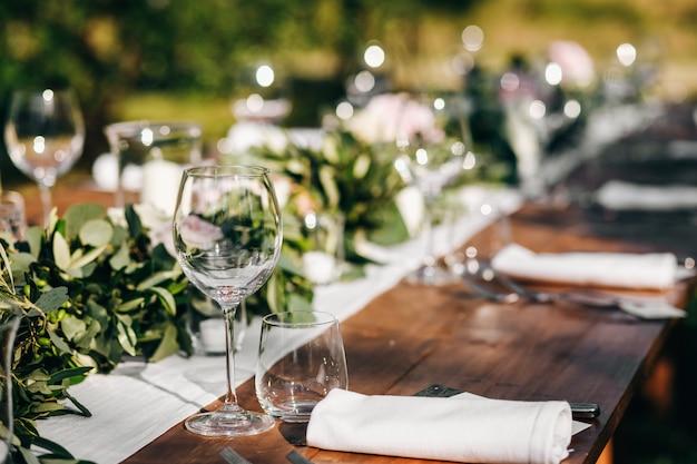 Guirnalda floral de eucalipto se encuentra en la mesa de la cena de la boda Foto gratis