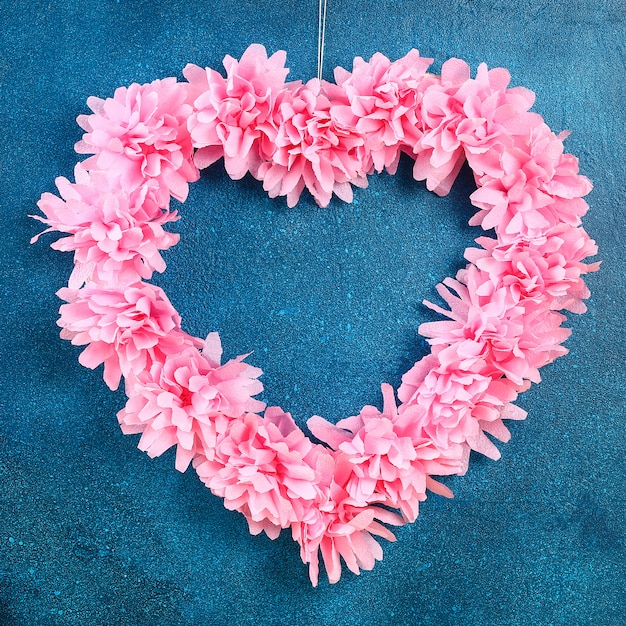 Guirnalda con forma de corazón decorada con flores artificiales hechas con pañuelos de papel rosa Foto Premium