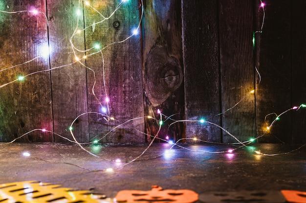 Guirnalda led de color en una pared de madera y calabazas talladas en papel naranja sobre la mesa. Foto Premium