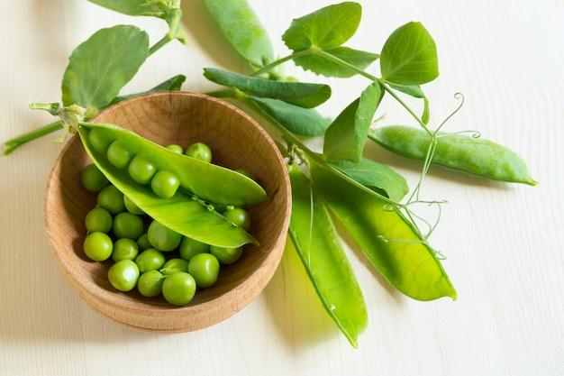Guisantes verdes jóvenes en superficie de madera blanca Foto Premium