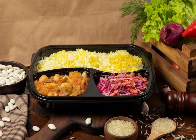 Guiso de ternera con papas y castañas en salsa de tomate con guarnición de arroz y para llevar ensalada de zanahoria para llevar Foto gratis