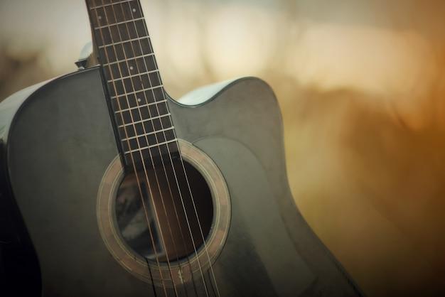 Guitarra acústica en un prado en el fondo del paisaje del atardecer Foto gratis