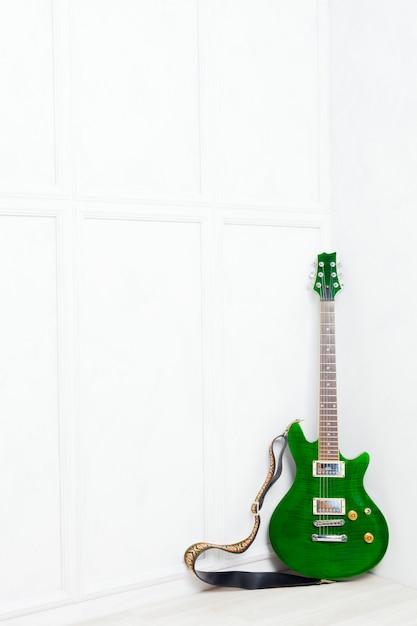 Guitarra apoyada frente a una pared blanca. Foto Premium