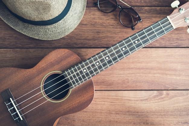 Guitarra ukulele en la mesa de madera | Foto Premium