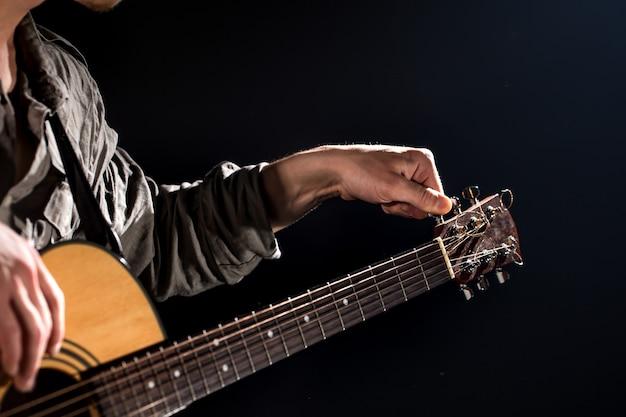 Guitarrista, música. un joven toca una guitarra acústica sobre un fondo negro aislado. luz puntiaguda Foto gratis