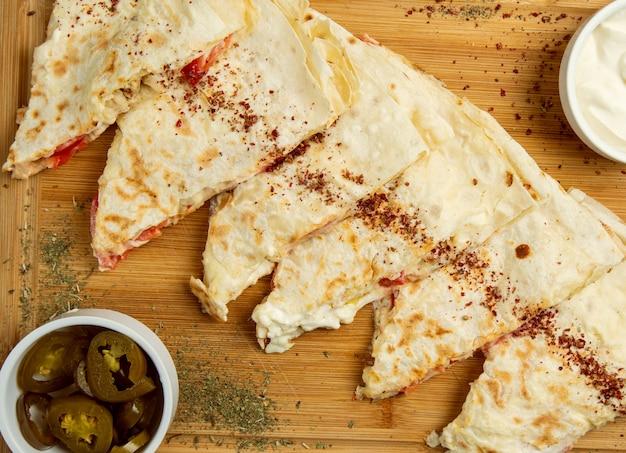 Gutab de carne tradicional, qutab, gozleme sobre tabla de madera con sumakh, turshu y yogurt. Foto gratis