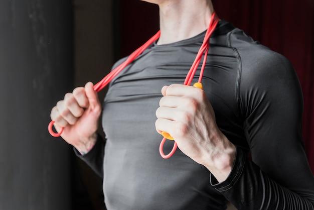Guy holding saltar la cuerda colocada en el cuello Foto gratis