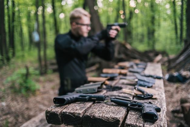 Guy in the woods prueba sus armas para disparar deportes Foto Premium