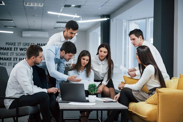 Guy muestra documento a una niña. grupo de jóvenes autónomos en la oficina conversando y trabajando Foto gratis