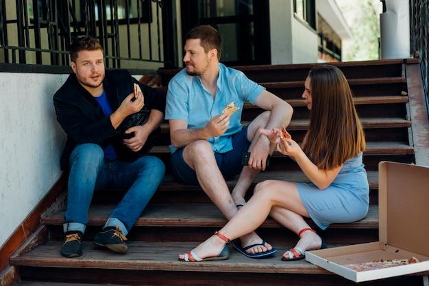 Habladores amigos comiendo pizza y sentados en las escaleras Foto gratis