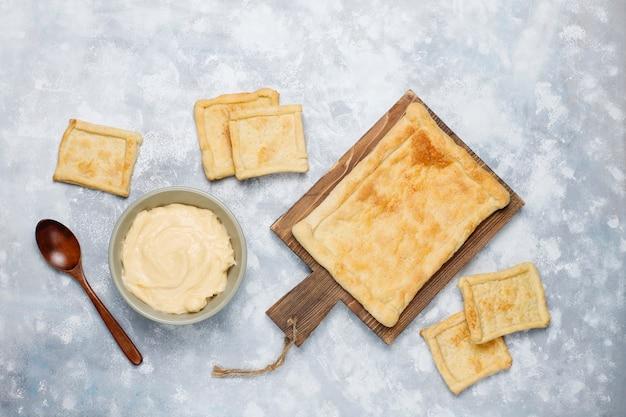 Hacer hojaldre delicioso y fresco con crema espesa en concreto, vista superior Foto gratis