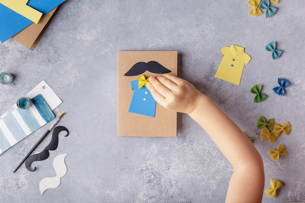Hacer tarjeta de felicitación para el día del padre. camisa con mariposa de pasta. tarjeta de papel. bigote Foto Premium